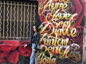 Une élève pose devant une fresque murale uqer