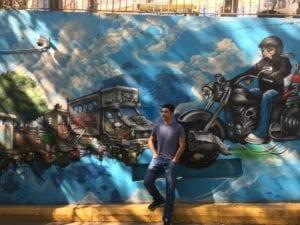 Un élève pose devant une fresque murale
