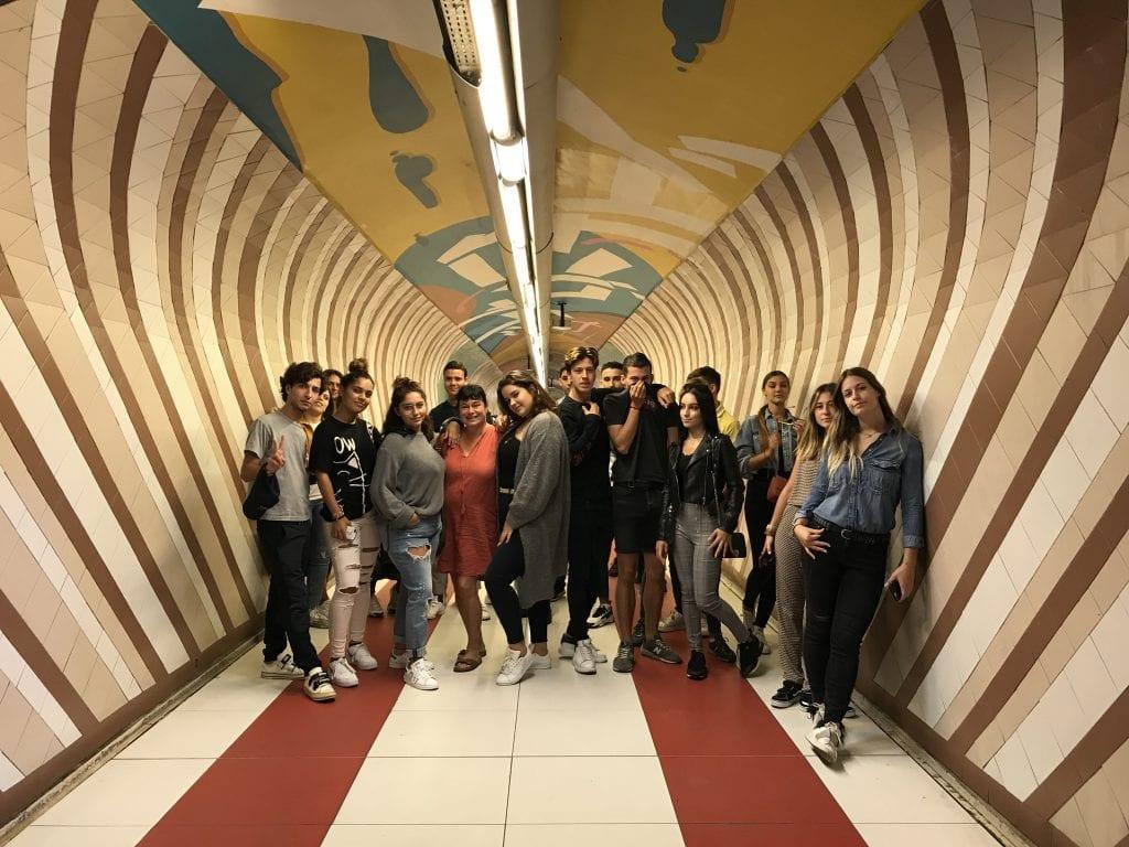 Groupe de jeunes posant dans un couloir coloré du métro