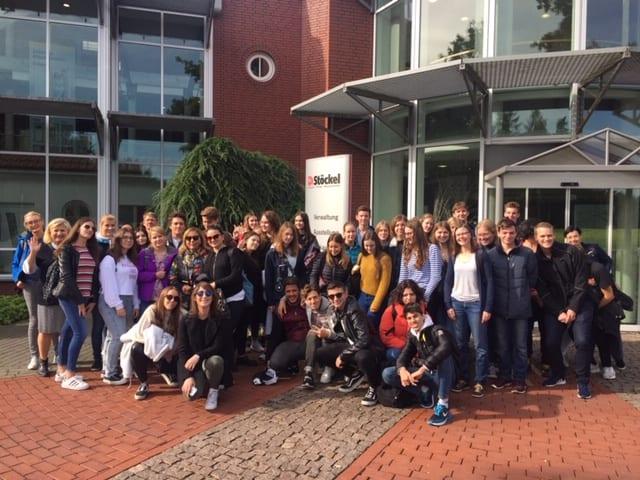 un groupe d'élèves et de professeurs devant un établissement scolaire allemand