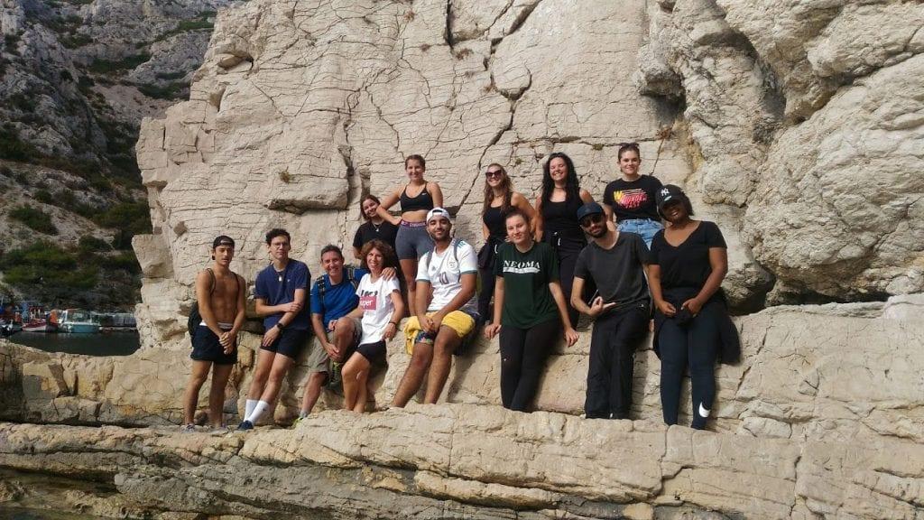 Un groupe de jeunes appuyé sur une roche du massif des calanques