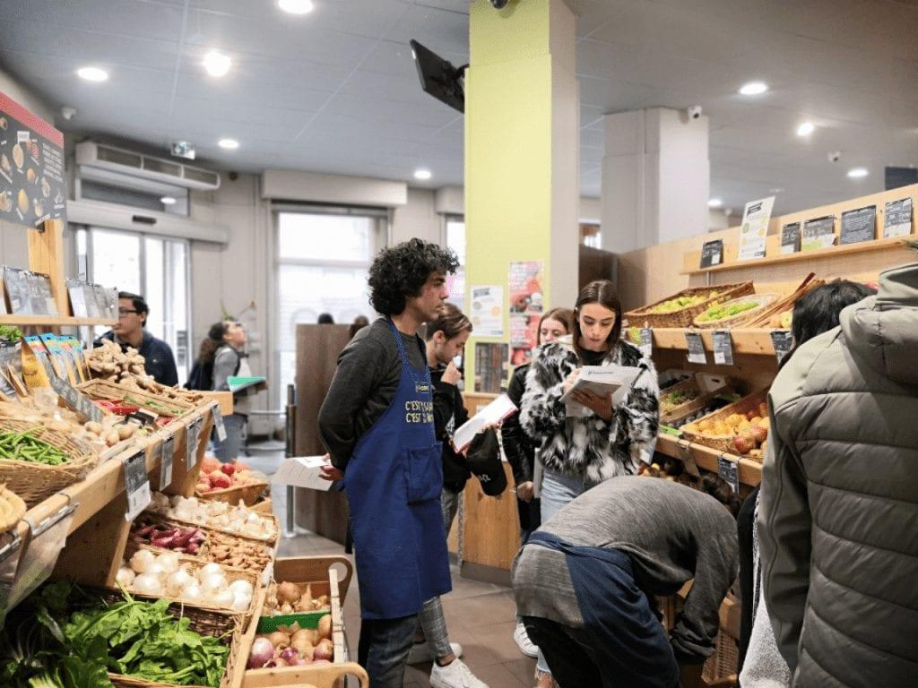 Photo d'un personnel BIOCOOP et de jeunes gens et de rayons de fruits et légumes rayons de fruits et légumes