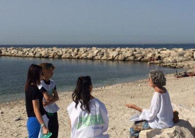 Des jeunes sur la plage avec des sacs en mainn